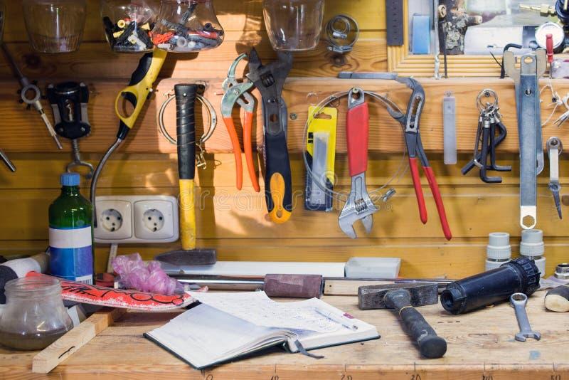 Träarbetsbänk på seminariet Lotten av olika hjälpmedel för diy och reparation arbetar Wood smutsig tabell med anteckningsboken Co arkivbild