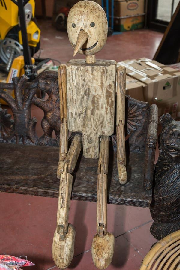 Träartikulerad docka som sitter på en bänk royaltyfri foto