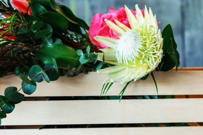 träask med blommor med vanlig hortensialilor, freesia, protea, rosor royaltyfria foton