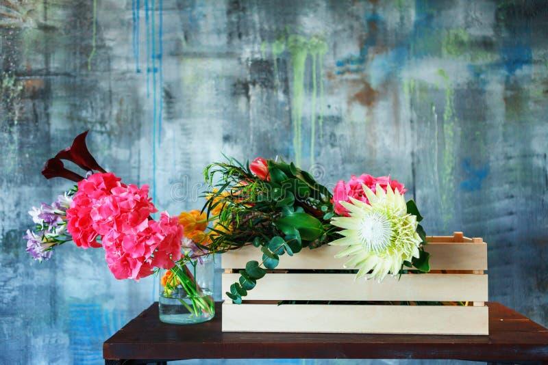 träask med blommor med vanlig hortensialilor, freesia, protea, rosor arkivbild