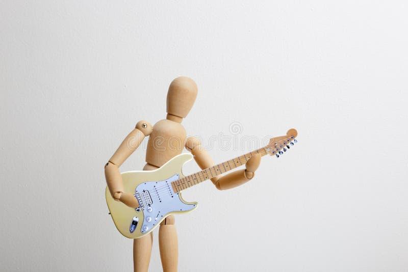 Träattrapp som spelar den elektriska gitarren arkivfoto