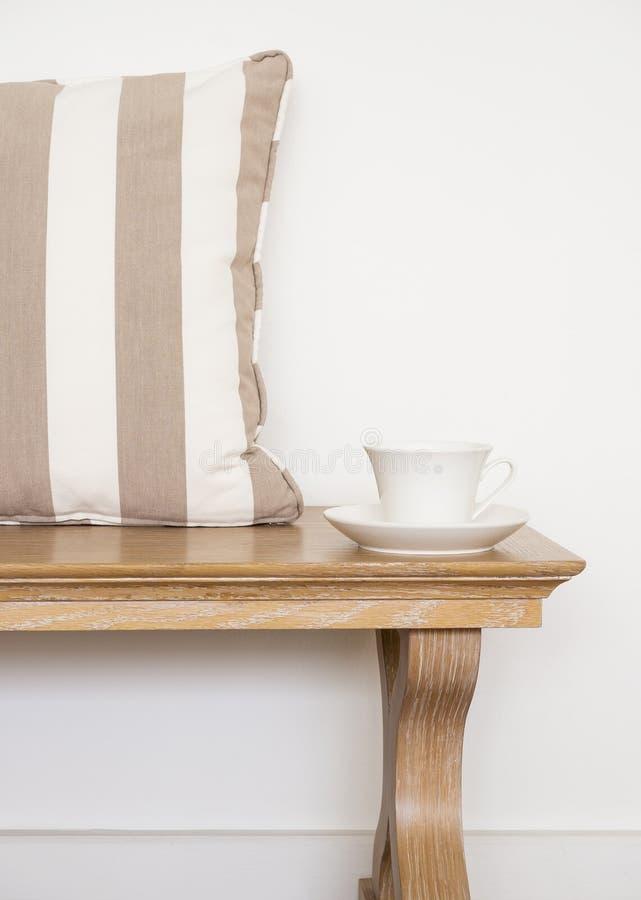 Träbänk med kaffe och kuddar i vardagsrum royaltyfri bild