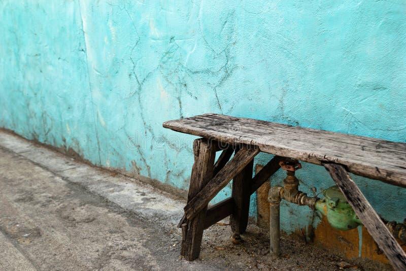Träbänk nära till den gamla spruckna blått- och vitväggen arkivfoto