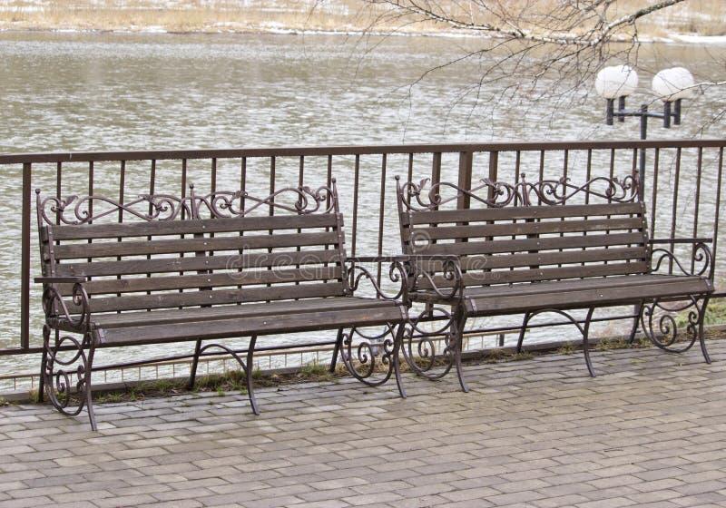 Träbänk och lykta på kajen av floden i dagsljuset arkivbilder