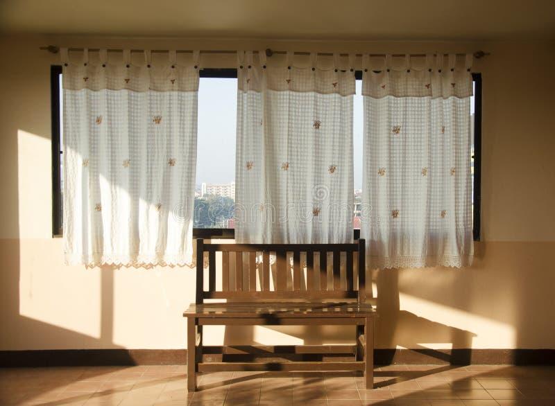 Träbänk på fönstret i hotell arkivbild