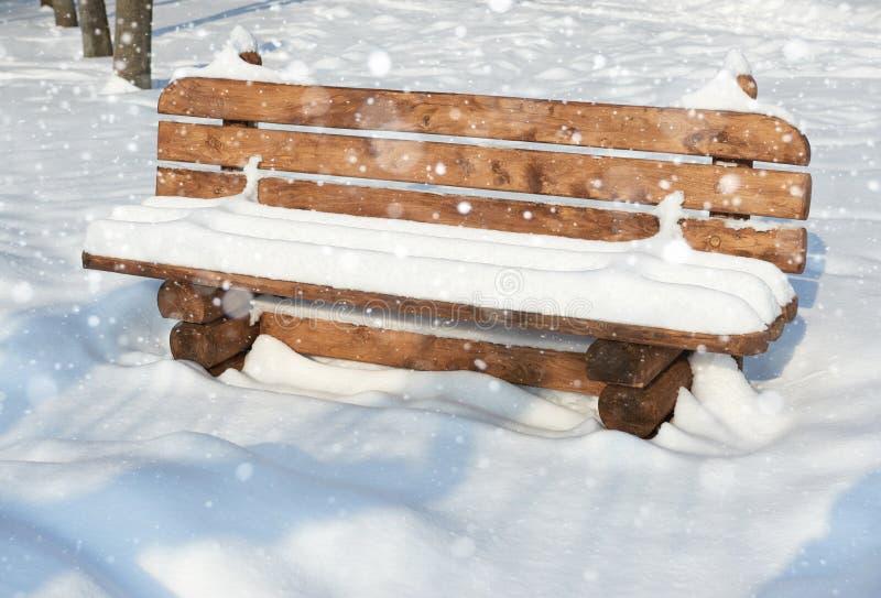 Träbänken i vintern parkerar Ljus solig dag och snö royaltyfri foto