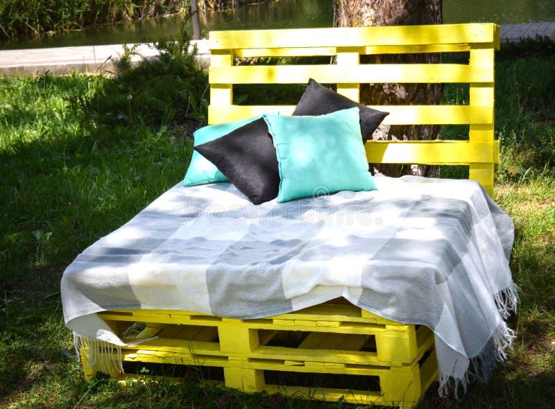 Träbänken som göras av gula paletter av fraktlastfall för sittin med kuddar, och plädet i parkerar Begreppet av fotografering för bildbyråer