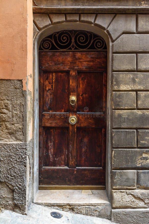 Träbågedörr på medeltida tegelstenbyggnad i Siena italy royaltyfria bilder