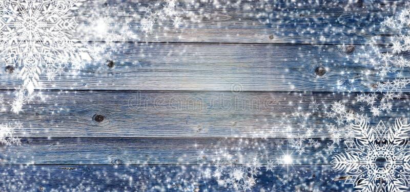 Träbakgrund för blå vinter med snöflingor omkring Jul kort för nytt år med kopieringsutrymme i mitten