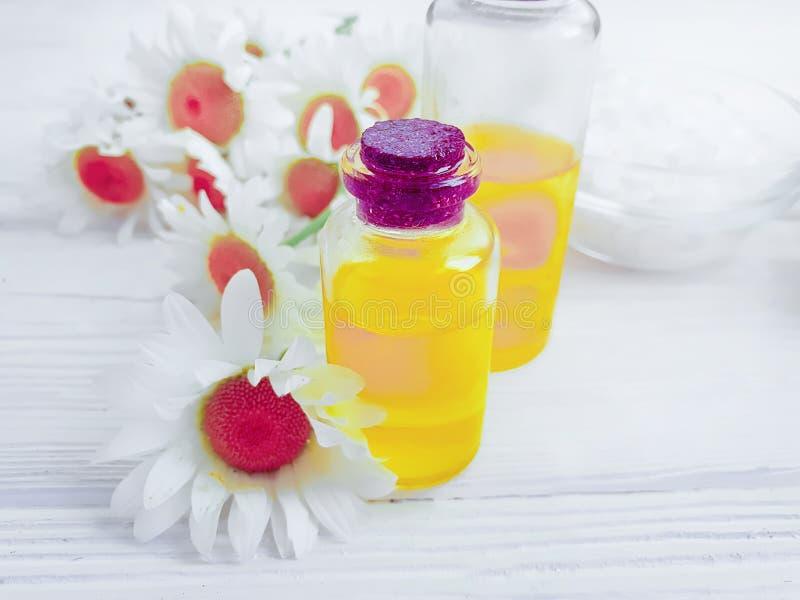 Träbakgrund för kosmetisk för extraktkamomill för olja sund blomma royaltyfri fotografi