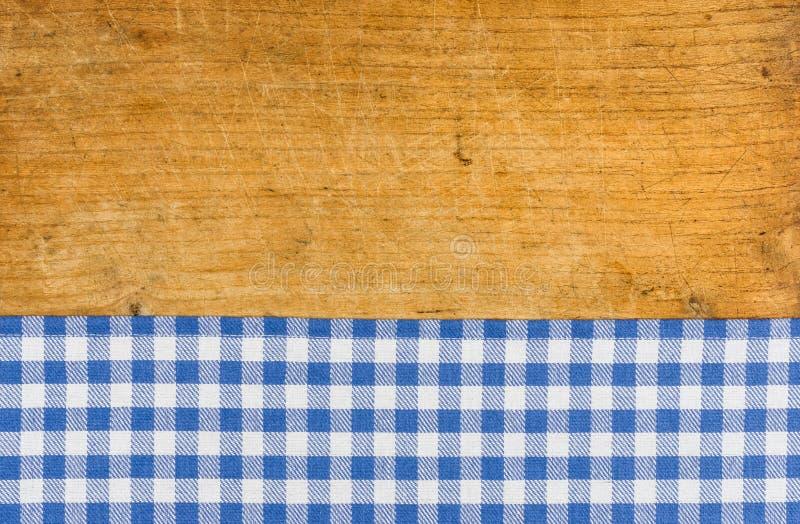 Träbakgrund med en blå rutig bordduk royaltyfri fotografi