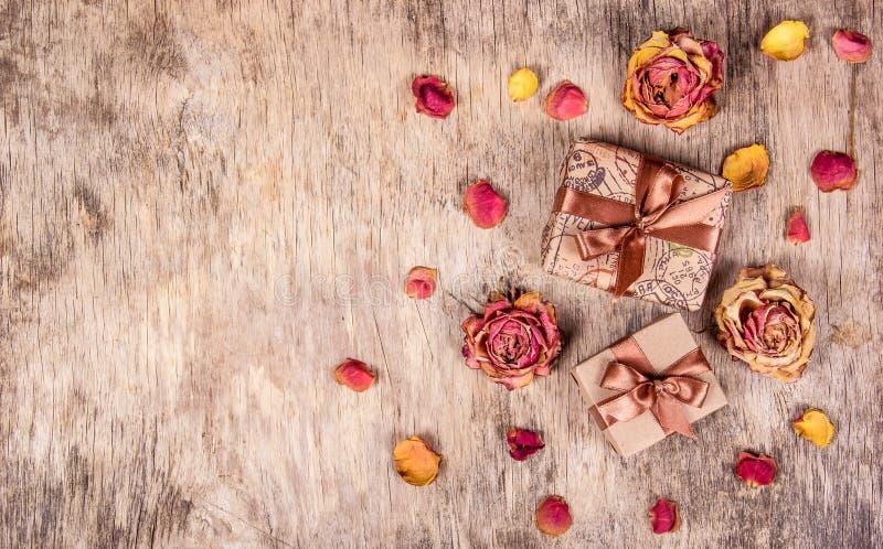 Träbakgrund med gåvan och rosor Torra blommor, torkade rosor royaltyfri bild