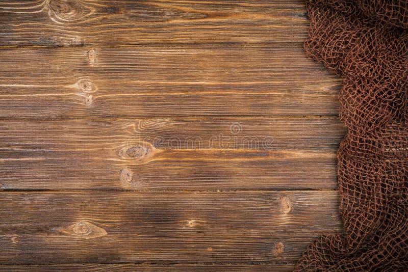 Träbakgrund med gammalt fisknät arkivfoto