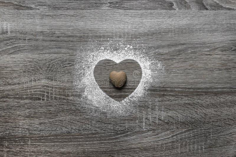 Träbakgrund med pudrad pulversnö en kontur av hjärtan hälls och ligger en kaka i form av en hjärta royaltyfri fotografi