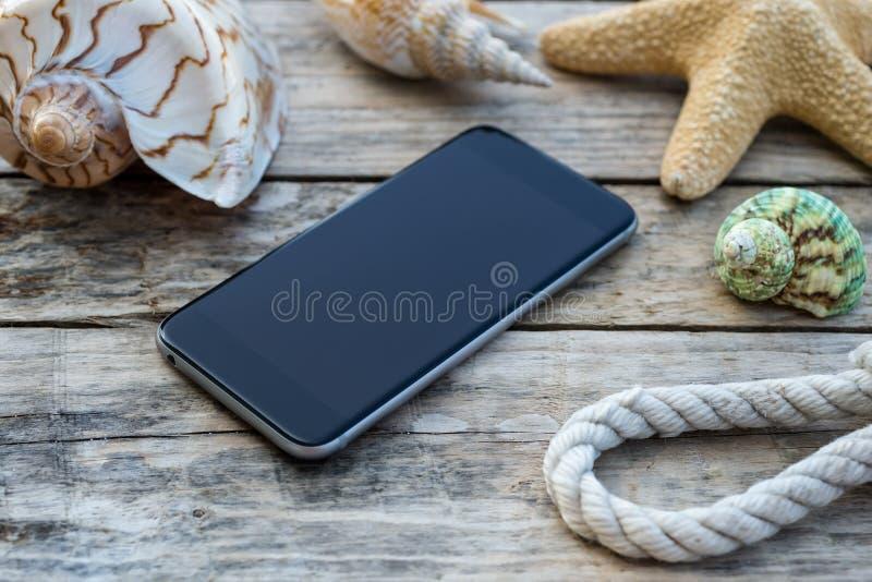 Träbakgrund med sjöstjärnan, telefonen och skalet royaltyfri bild