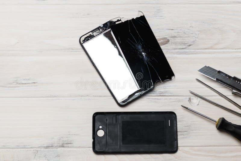 träbakgrund på den är den brutna telefonen broken exponeringsglas skruvmejsel kniv mobiltelefonreparationsbegrepp royaltyfria bilder