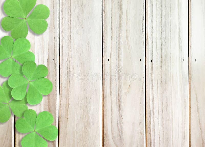 Träbakgrundstextur med det gröna treklöverväxt av släktet Trifoliumbladet på vänstra sidan för Sts Patrick dag royaltyfri fotografi