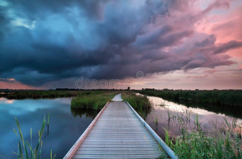Träbanabro över floden på den stormiga solnedgången royaltyfri foto