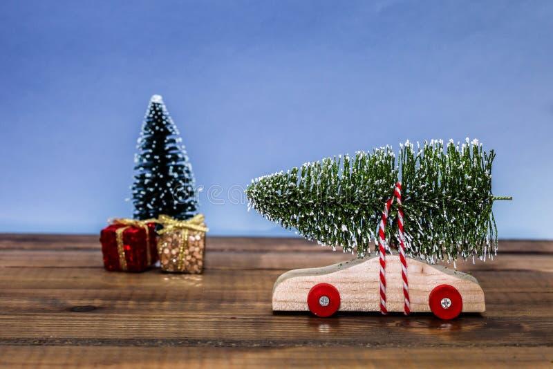 Träbil med julträdet och gåvaaskar arkivfoton