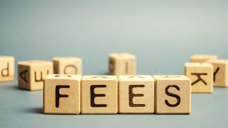 Träblock med ordet Avgifter och slumpmässigt utspridda kuber Fast pris som debiteras för en viss tjänst Affärsverksamhet och fina arkivfoto