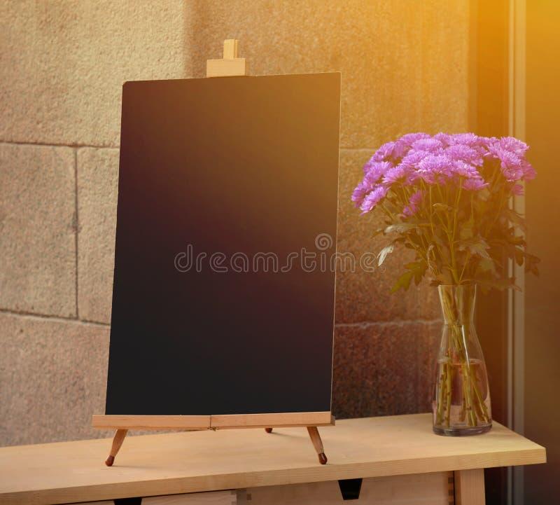 Träbräde för restaurangmeny med tomt utrymme som tillfogar textanseende på restaurangingången med blomkrukan royaltyfri fotografi