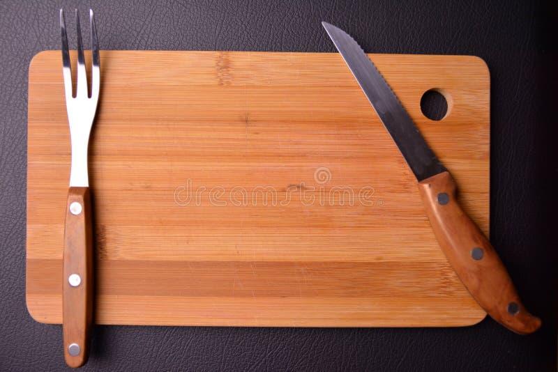 träbräde i köket med gaffeln och kniven fotografering för bildbyråer