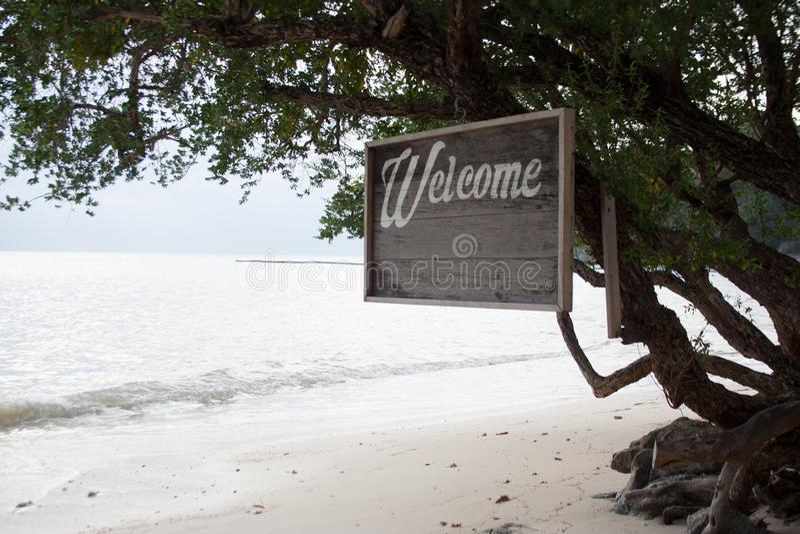 Träbräde med ett ord 'välkomnande 'på en tropisk strand arkivbilder
