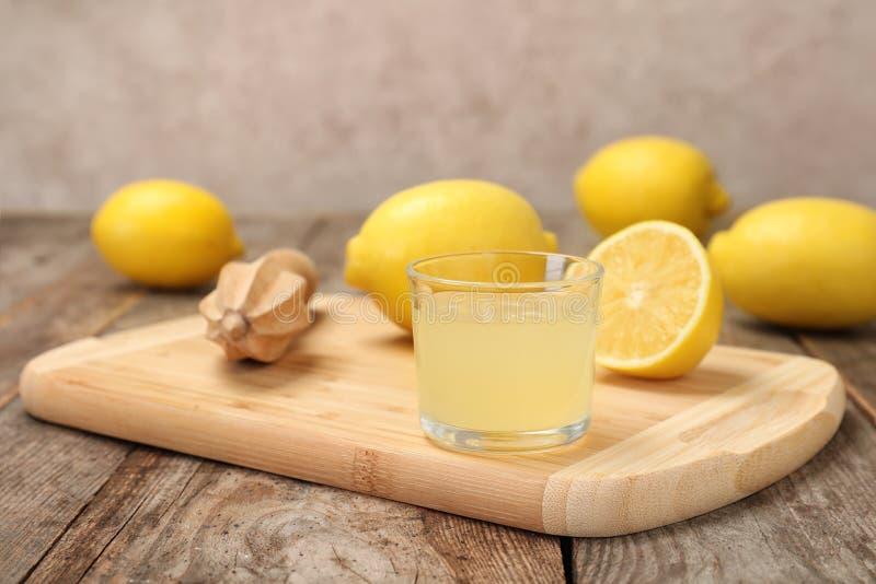 Träbräde med exponeringsglas av den nytt sammanpressade citronjuice och reameren arkivbilder