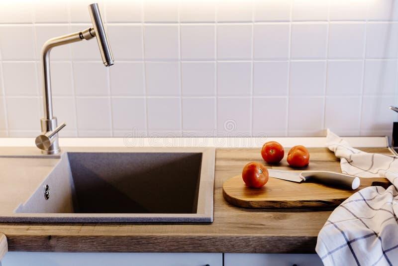 Träbräde med kniven, tomater, handduk, kryddor på modern kitch royaltyfria foton