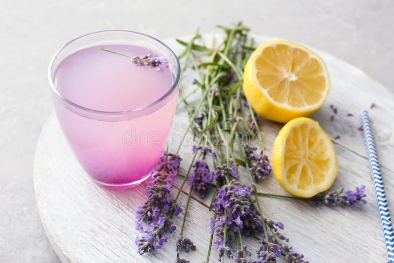 Träbräde med lavendellemonad i exponeringsglas och ingredienser på grå bakgrund fotografering för bildbyråer