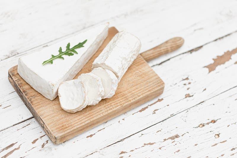 Träbräde med olik ost på vit bakgrund Stycken av ostar p? woodenplatter kopiera avst?nd arkivbild
