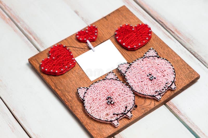 Träbräde med rosa svin och röda hjärtor och textram på vit trädiagonal bakgrund kopiera avst royaltyfri bild