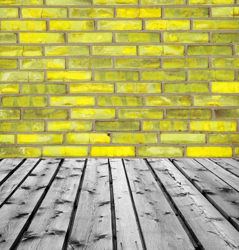 Träbräden och gul tegelstenvägg royaltyfri bild