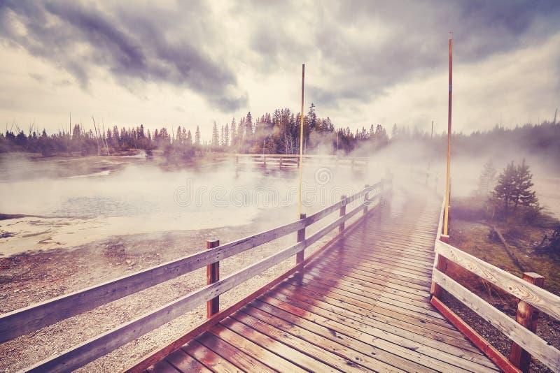 Träbro över ångande terräng i den Yellowstone nationalparken arkivfoton