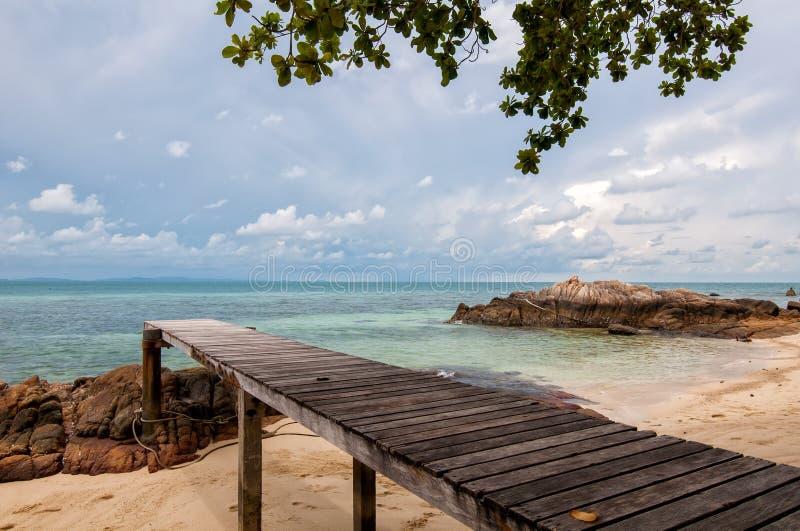 Träbro in i havet Thailand arkivbild