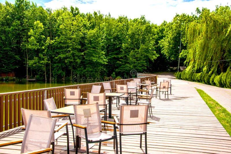 Träbro med ett staket som tabeller och stolar lokaliseras på Sommarkaf? Det ?r sommar utanf?r Solen ?r gl?nsande royaltyfria foton