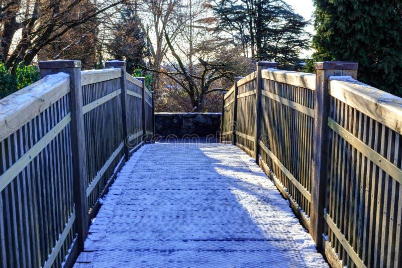 Träbro med snöig yttersida i drottningen Elizabeth Park arkivfoto