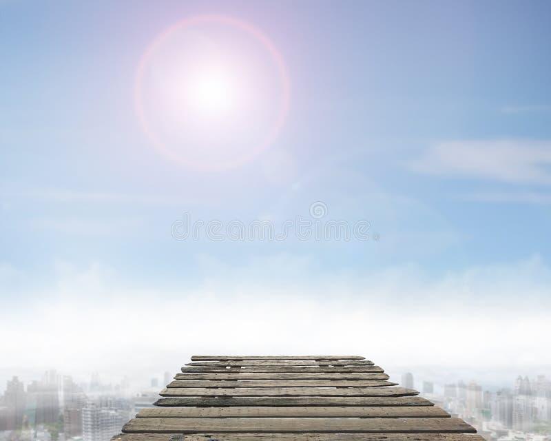 Träbro med solig himmelcityscapebakgrund arkivbild