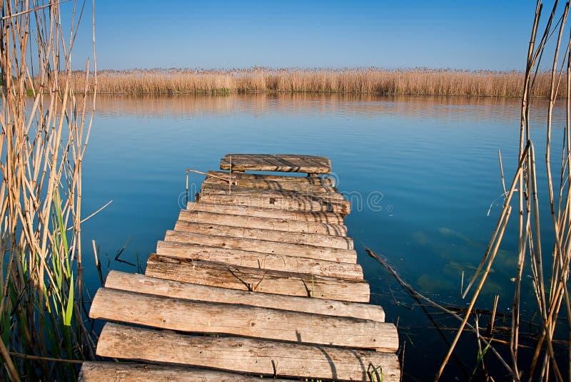 Träbro på den lugna floden arkivbild
