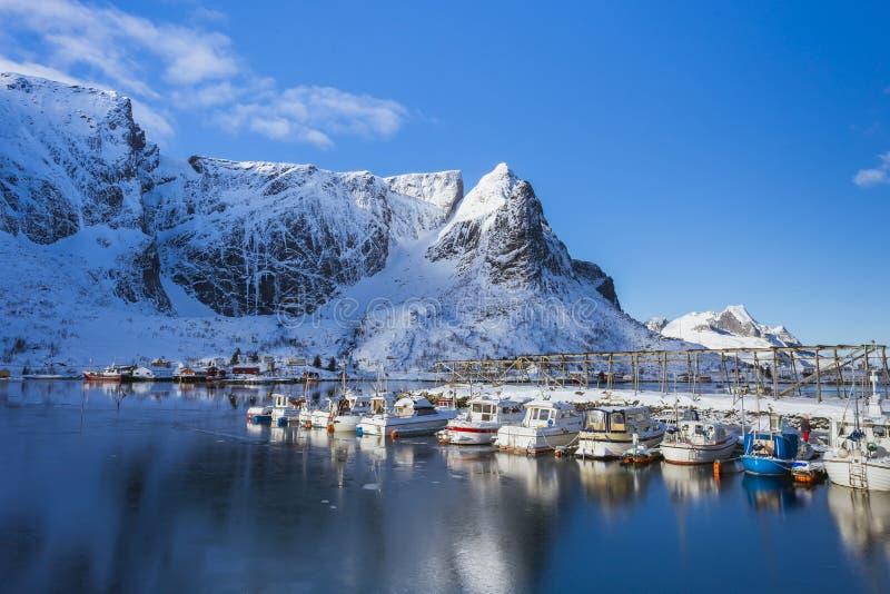 Träbro på vattnet som leder till byn på Lofoten öar i Norge arkivbild