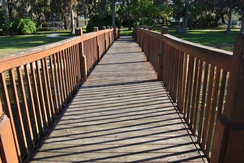 Träbro som leder till Willow Tree Park royaltyfri foto