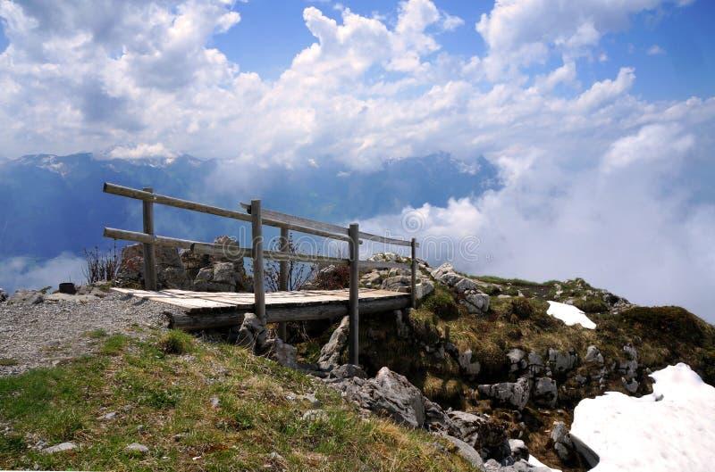 Träbron som leder till molnen i schweiziska fjällängar arkivfoton