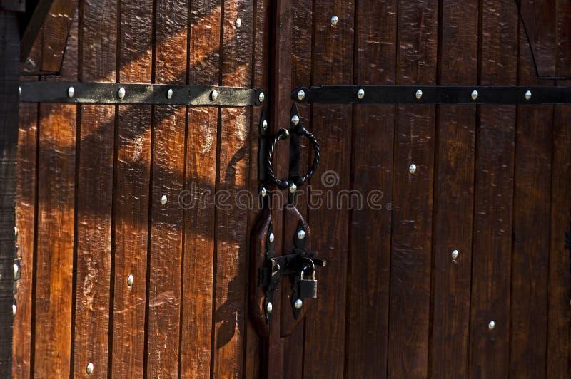 Träbruna röda portar, dörrar som stängs till den försåg med gångjärn slotten arkivbild