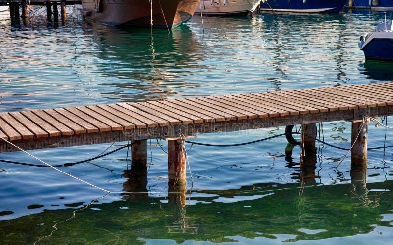 Träbrygga över vatten i port arkivfoton