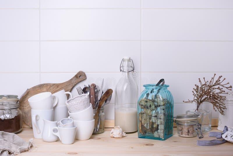 Träbufféräknaren med kitchenware, sötsaker, mjölkar flaskan och malt kaffe Vit bakgrund royaltyfri foto