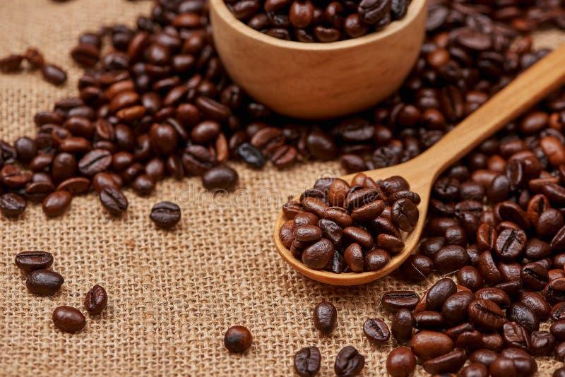 Träbunke med grillade kaffebönor på lantlig bakgrund arkivfoton