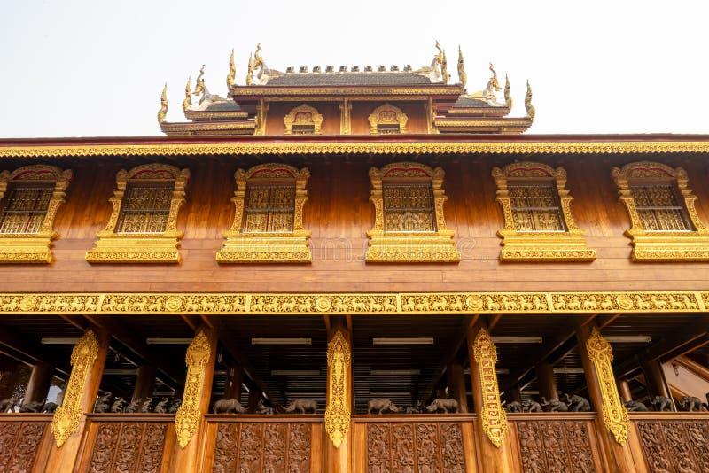 Träbyggnad för härlig thailändsk stil med åtskilliga fönster med guld- ramar i en buddistisk tempel i Thailand arkivfoto