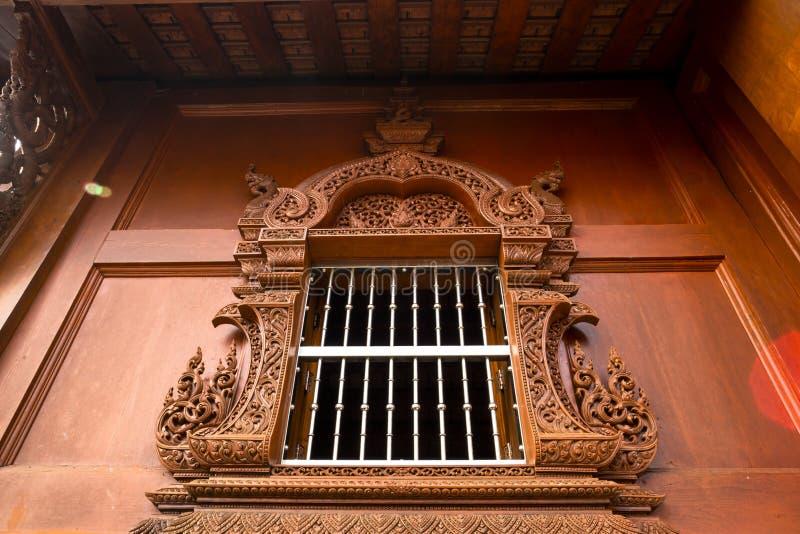 Träbyggnad för thailändsk stil med den härliga sned fönsterramen på en buddistisk tempel i Thailand royaltyfria foton