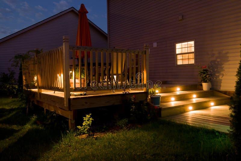 Trädäck och uteplats av familjhemmet på natten royaltyfria bilder