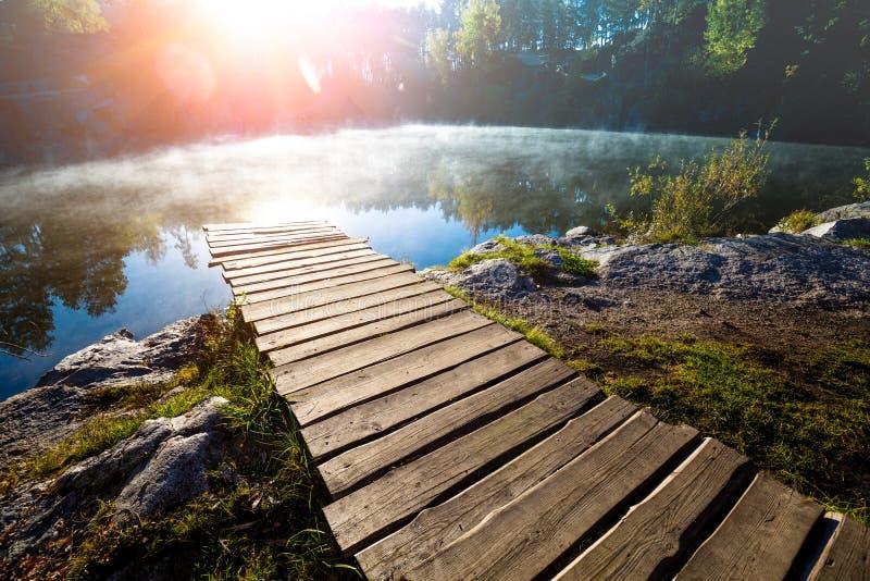 Trädäck på det stenigt lakeshore royaltyfri foto